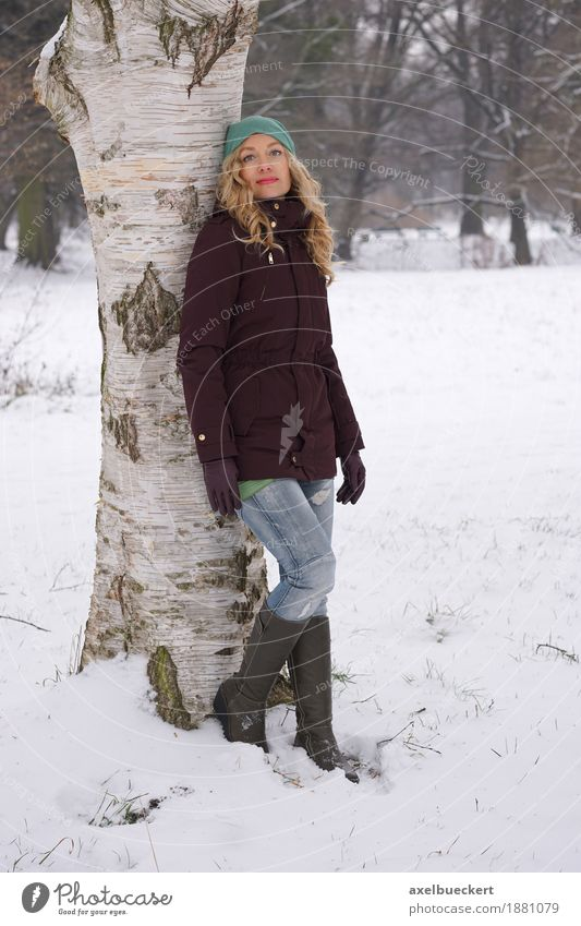 woman leaning against tree in winter Lifestyle Leisure and hobbies Winter Snow Human being Feminine Woman Adults 1 30 - 45 years Nature Tree Park Forest Fashion