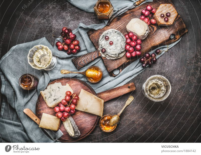 Various cheeses on cutting boards with grapes and wine Food Cheese Dairy Products Fruit Dessert Nutrition Buffet Brunch Banquet Beverage Wine Crockery Knives