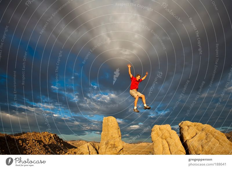 Rock climber on the summit. Human being Man Adults Freedom Jump Mountain Flying Tall Hiking Dangerous Adventure Peak Footwear Climbing Environment