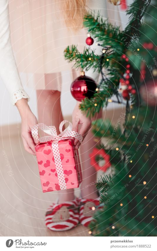 Closeup of girl getting Christmas gift from under a tree Human being Child Christmas & Advent Tree Red Girl Lifestyle Feasts & Celebrations Pink Infancy Gift
