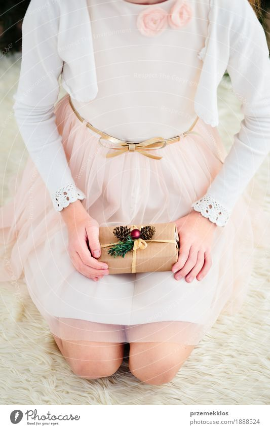 Girl holding Christmas gift and sitting on a carpet Lifestyle Feasts & Celebrations Christmas & Advent Child Human being 1 8 - 13 years Infancy Dress Pink Red