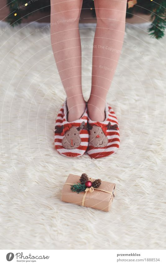 Girl standing by Christmas gift put near tree Lifestyle Feasts & Celebrations Christmas & Advent Child Human being Legs 1 Dress Red Anonymous Carpet christmas
