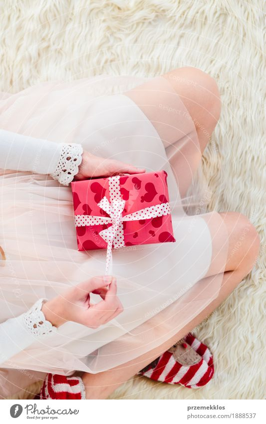 Girl holding Christmas gift on legs and sitting on a carpet Human being Child Christmas & Advent Hand Red Girl Lifestyle Legs Feasts & Celebrations Pink Infancy Gift Dress 8 - 13 years Home Story