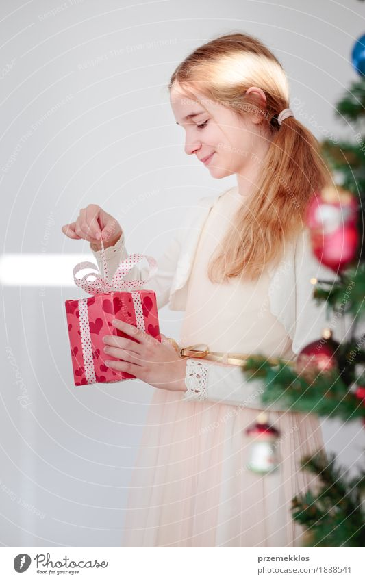 Happy girl unpacking Christmas gift standing behind a tree Human being Child Christmas & Advent Tree Girl Lifestyle Happy Feasts & Celebrations Pink Infancy Smiling Gift Dress 8 - 13 years Home Vertical