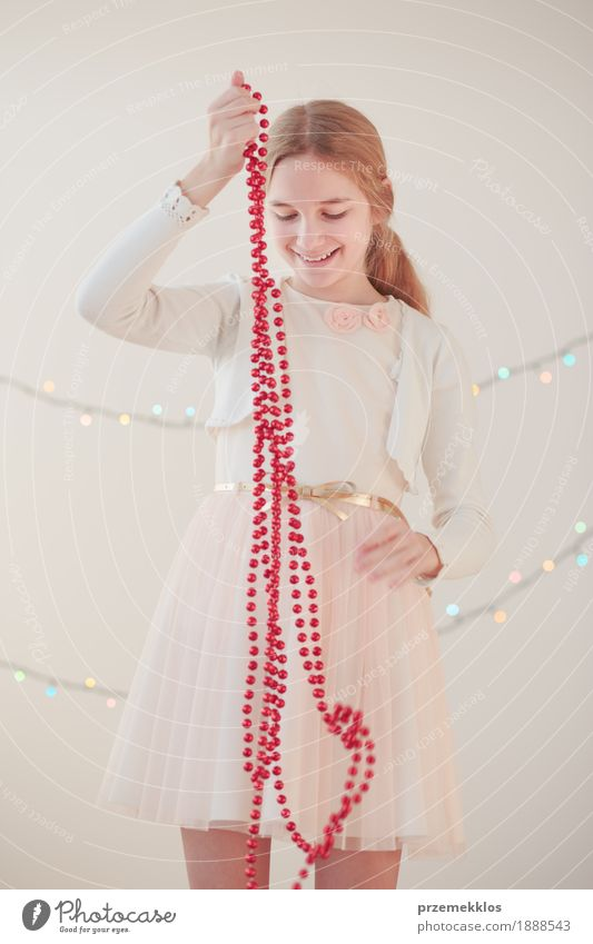 Portrait of young girl unwrapping red Christmas decorations Human being Child Youth (Young adults) Christmas & Advent Joy Girl Lifestyle Happy