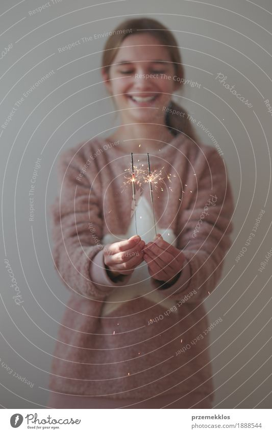 Young smiling girl celebrating New Year holding sparklers Human being Child Youth (Young adults) Christmas & Advent Joy Girl Warmth Lifestyle Happy