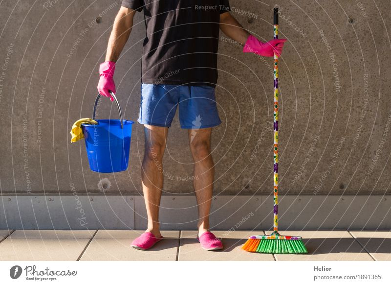 A househusband in pink slippers and cleaning utensils Summer Masculine Man Adults Legs 1 Human being 30 - 45 years Wall (barrier) Wall (building) T-shirt