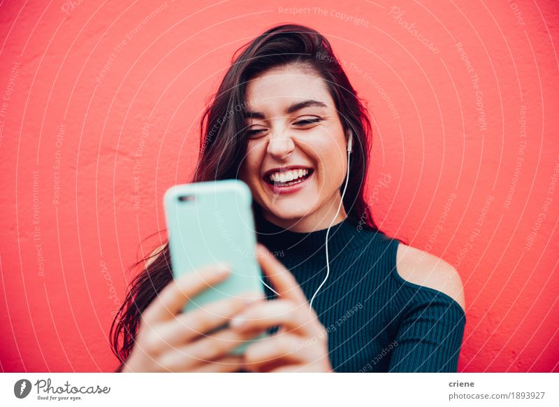 Young happy women video chatting with smart phone Human being Youth (Young adults) Colour Young woman Red Joy 18 - 30 years Adults To talk Lifestyle Feminine Laughter Modern Music Technology Telecommunications