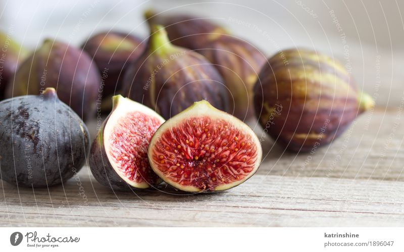 Fresh fruits - figs on the wooden table Fruit Diet Exotic White background close Cut Fig food Organic Purple ripe seed Slice sweet Consistency Vitamin Wedge