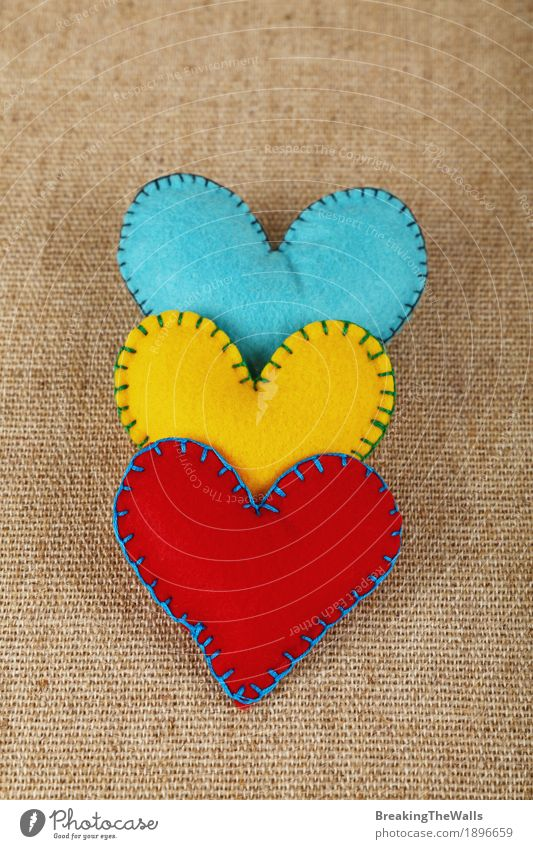Three handmade felt hearts, yellow, red and blue on canvas Leisure and hobbies Handicraft Handcrafts Family & Relations Art Cloth Heart Love Together Natural