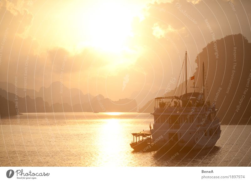 Sunrise behind boat in Ha Long Bay, Vietnam Vacation & Travel Adventure Exotic Nature Halong bay Iceland Sunset World Heritage Site Watercraft Clouds Hill Idyll
