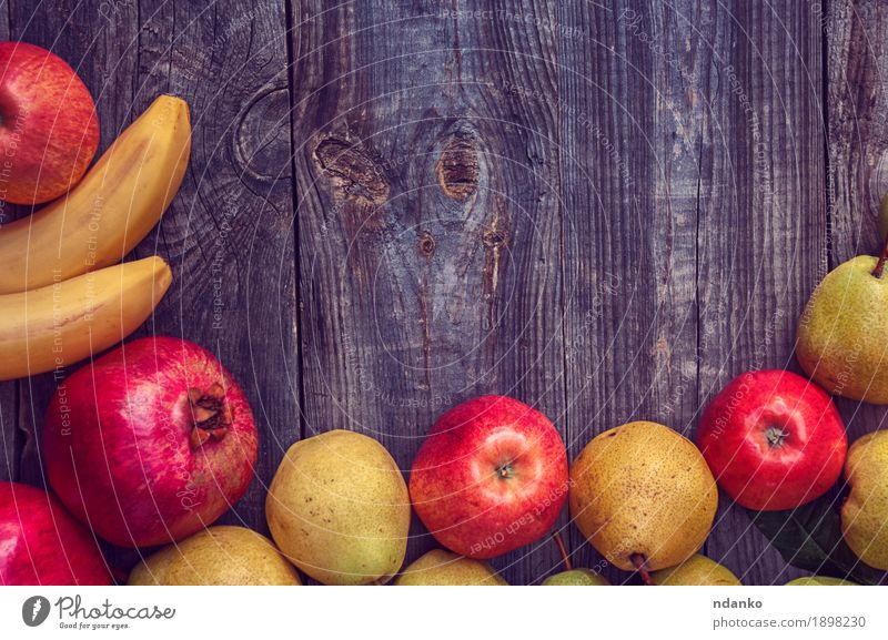 Bananas, pomegranates, apples and pears on a gray wooden surface Fruit Apple Organic produce Vegetarian diet Garden Table Autumn Wood Fresh Natural Above Juicy