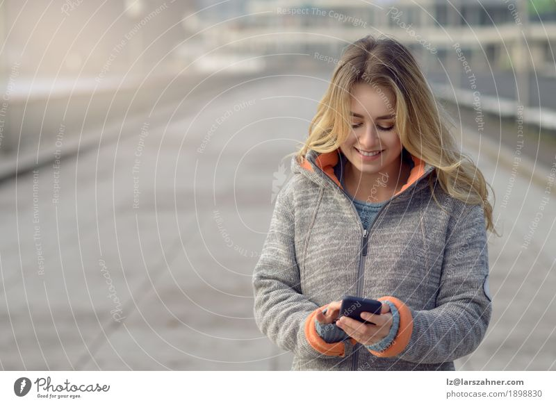 Young woman with mobile phone walking a city street Human being Woman Vacation & Travel Youth (Young adults) Town Beautiful Winter 18 - 30 years Adults Street Lifestyle Fashion Transport Modern Action Technology