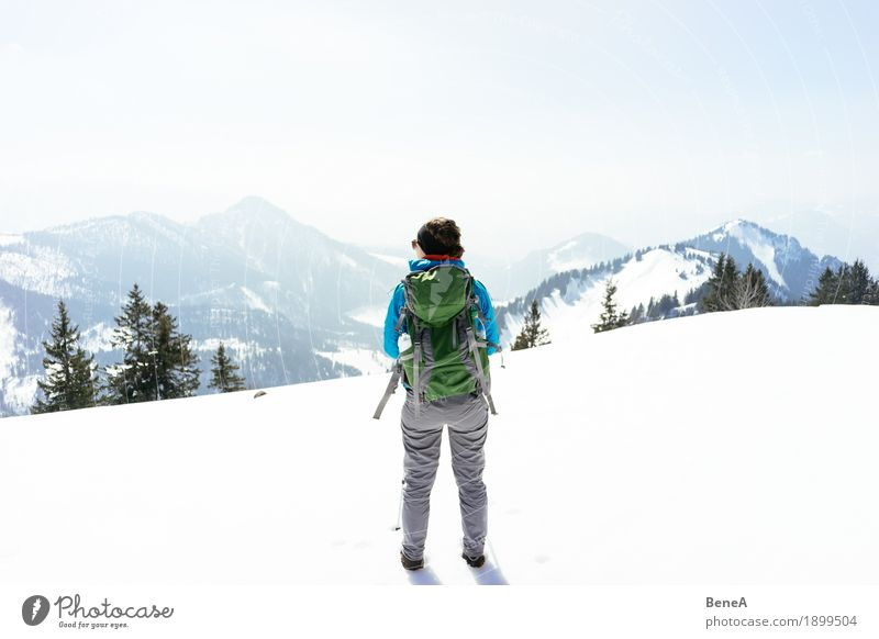 Woman standing in a wintery mountain landscape in the snow at Hochries Relaxation Vacation & Travel Winter Sports Adults Nature Fitness Adventure