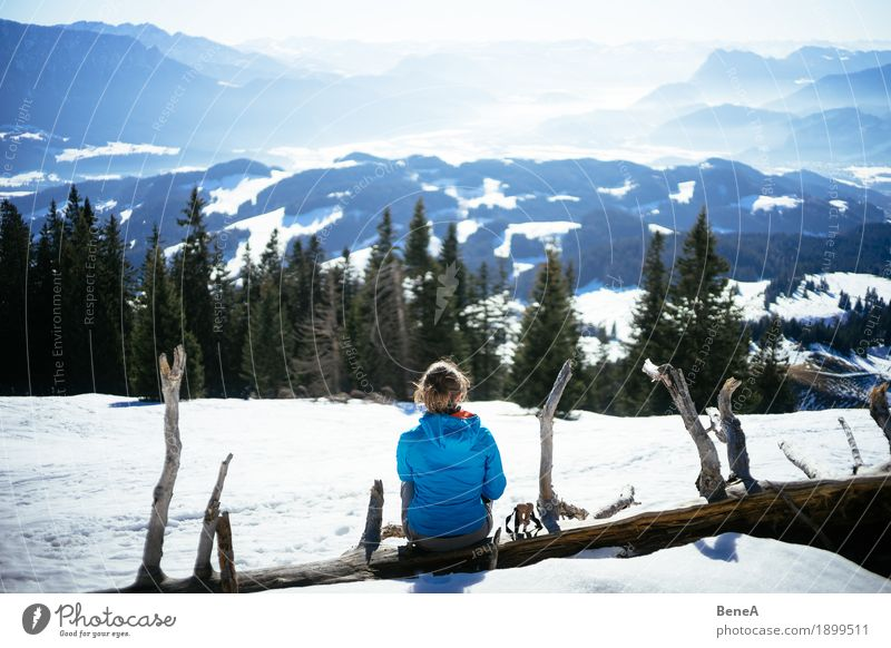 Woman sitting on a tree trunk at a pointed stone and looking into the Inn valley Relaxation Vacation & Travel Winter Adults Nature Fitness Contentment