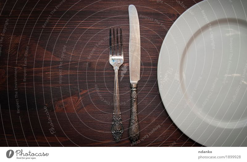 Half empty white plates, vintage knife and fork Old White Dish Wood Brown Above Retro Vantage point Table Crockery Plate Top Knives Silver Beige