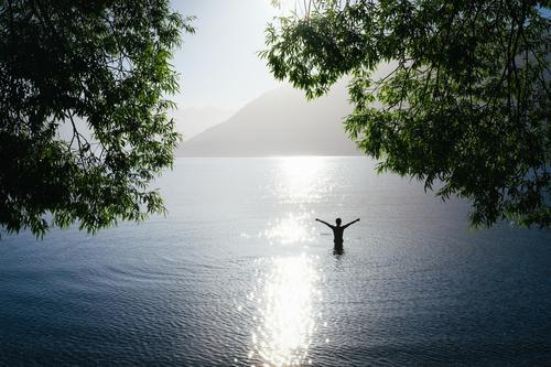 Person in a lake in backlight stretches arms into the air Joy Relaxation Adventure Far-off places Freedom Expedition Camping Summer Summer vacation Sun
