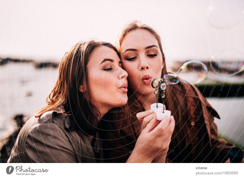 Teenage girls having fun blowing bubbles together Human being Youth (Young adults) Beautiful Young woman Joy 18 - 30 years Adults Emotions Lifestyle Feminine Happy Freedom Together Friendship 13 - 18 years To enjoy