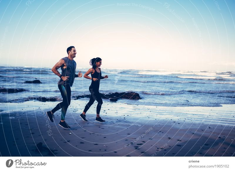 Fit caucasian young adult couple running on beach Lifestyle Joy Body Athletic Leisure and hobbies Summer Beach Ocean Sports Jogging Human being Young woman
