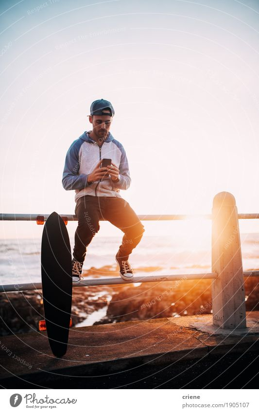 Young adult man sitting on railing browsing with smart phone Human being Youth (Young adults) Young man To talk Lifestyle Sports Masculine Sit Technology Telecommunications Wait Telephone Internet Cellphone Information Technology Skateboard