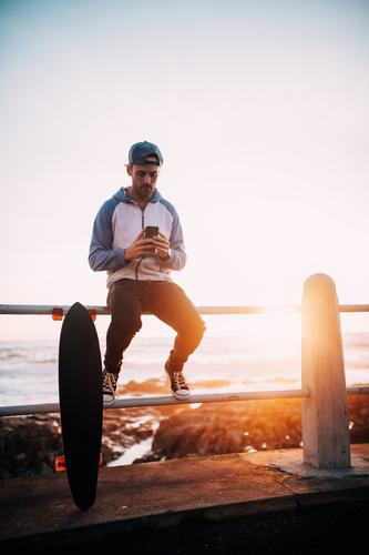 Young adult man sitting on railing browsing with smart phone Human being Youth (Young adults) Young man To talk Lifestyle Sports Masculine Sit Technology