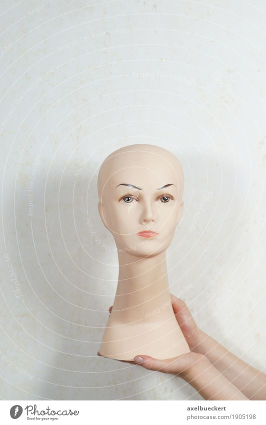doll's head Beautiful Feminine Hand Bald or shaved head Doll Plastic To hold on Mannequin Presentation Head False Colour photo Subdued colour Interior shot