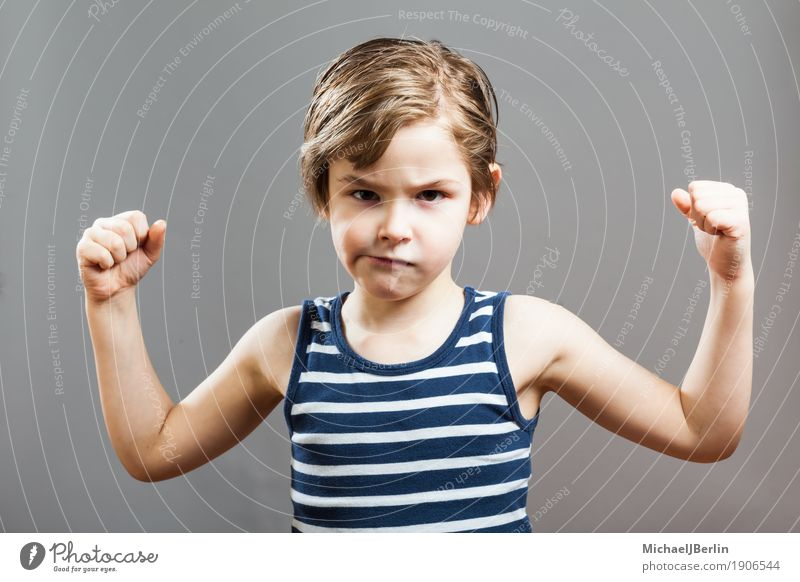 Six-year-old boy shows his biceps muscles Face Sports Success Child Human being Toddler Boy (child) 3 - 8 years Infancy Growth Athletic Cool (slang) Strong Gray