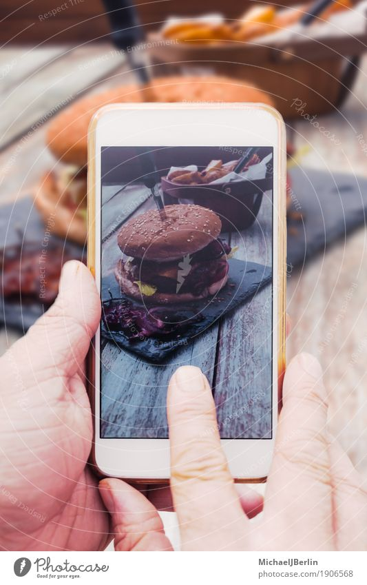 Hand with smartphone mobile phone, photo of Burger on table Food Meat Bread Roll Cheeseburger Bacon social media share Internet Table Telephone Cellphone PDA
