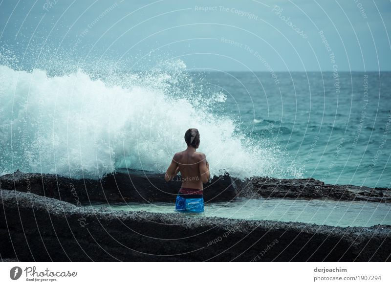 Eco shower. A man stands on the beach and a wave crashes over him. One day in January on Pacific Joy Fitness Wellness Leisure and hobbies Trip Aquatics