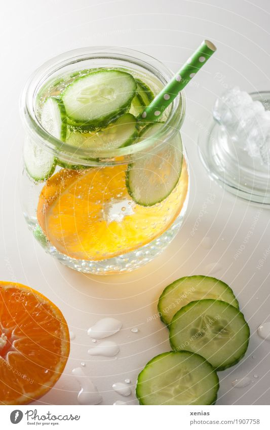 A glass of soft drink with tangerine, cucumber and straw on white background Beverage Cold drink Tangerine Fruit Slices of cucumber detox Drinking