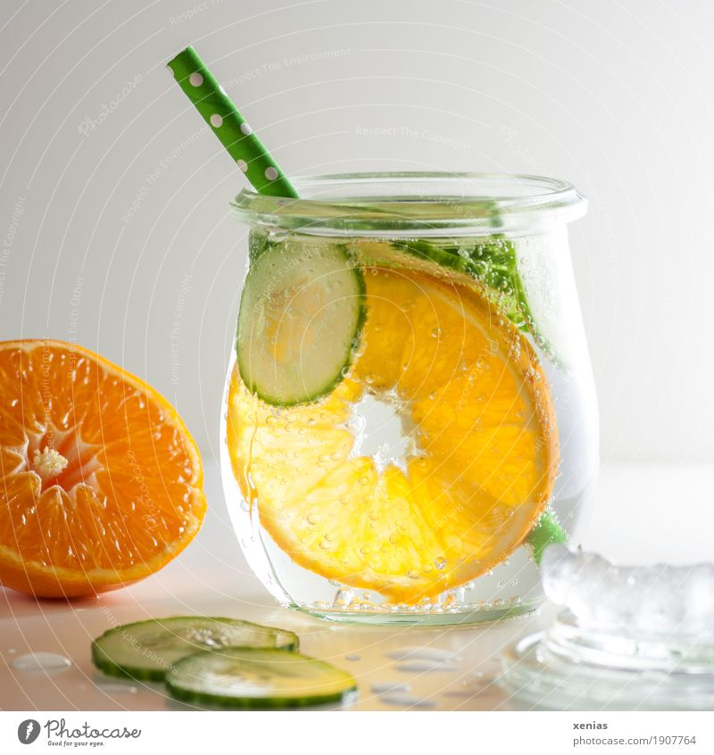Cool soft drink with mineral water, tangerine, cucumber slices, ice cubes and green straw Cold drink Tangerine Slices of cucumber Ice cube Beverage Drinking
