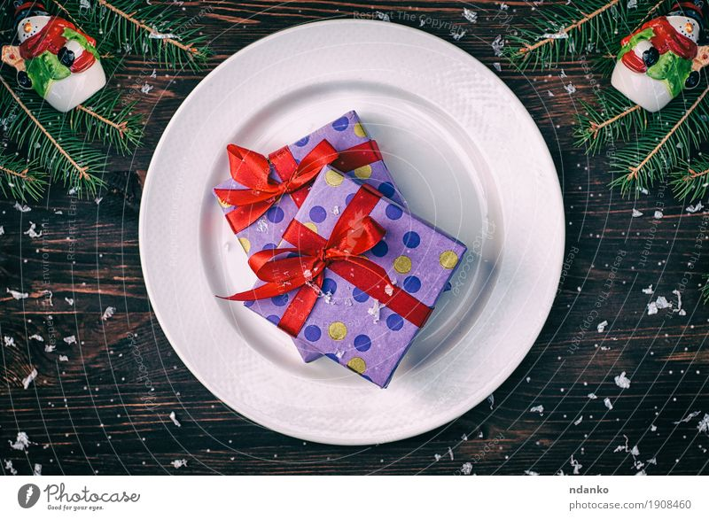 Two gift wrapped in paper with a red ribbon on a white plate Old Christmas & Advent White Red Winter Dish Snow Wood Feasts & Celebrations Brown Above Decoration