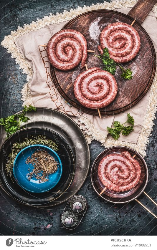 Bratwurst on vintage cutting board with herbs and spices Food Meat Sausage Herbs and spices Cooking oil Nutrition Picnic Organic produce Beverage Crockery Style