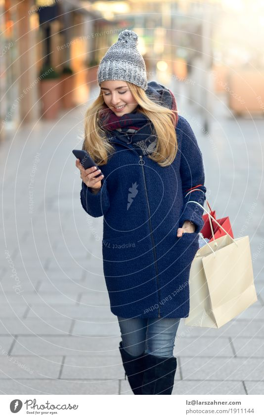 Fashionable young woman busy with her mobile phone Human being Woman Youth (Young adults) Town Beautiful Winter 18 - 30 years Adults Lifestyle Modern Action