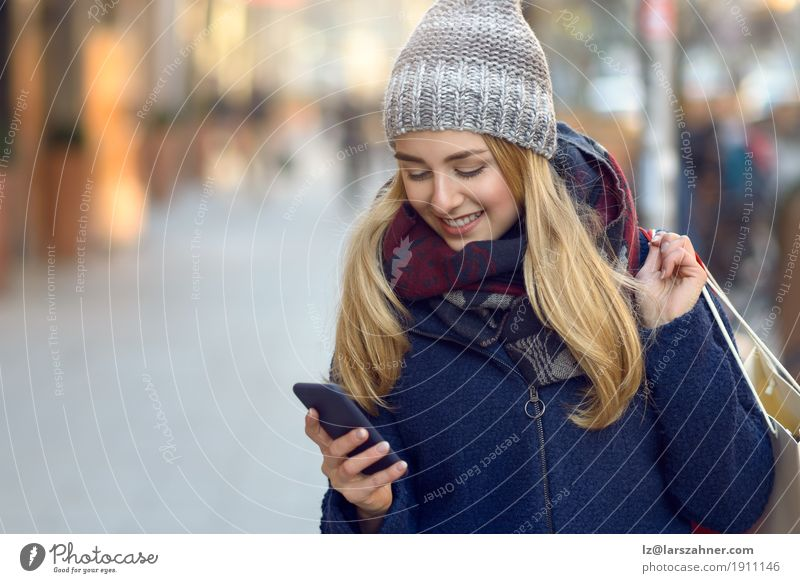 Fashionable young woman busy with her mobile phone Human being Woman Youth (Young adults) Town Beautiful Winter 18 - 30 years Adults Lifestyle Fashion Modern Action Technology Smiling Reading Telephone