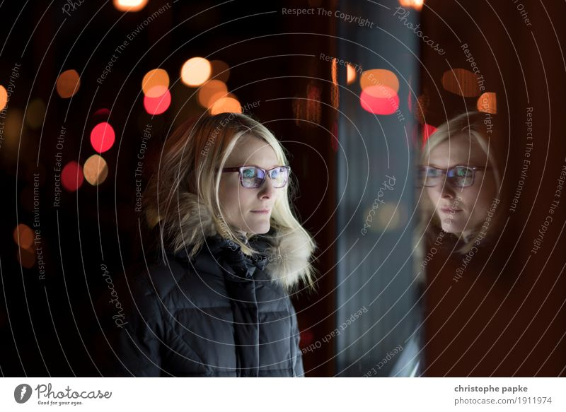 reflections City trip Woman Adults 1 Human being Blonde Glass Looking Shop window Blur Point of light Eyeglasses Winter Colour photo Subdued colour