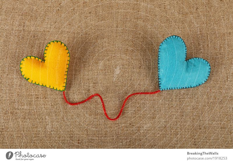 Two stitched felt hearts with red twine on canvas Blue Red Yellow Emotions Love Natural Art Together Leisure and hobbies Creativity Vantage point Heart Romance