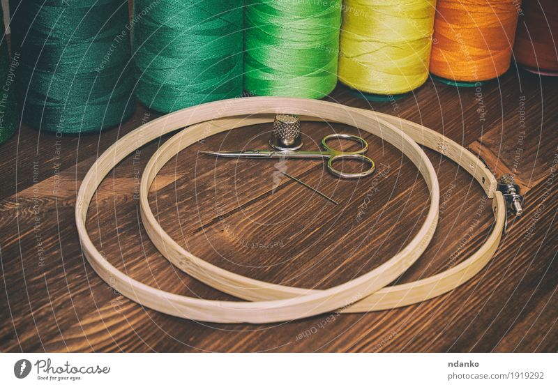 colored thread in the coils with wooden hoops for embroidery Colour Green Red Yellow Wood Fashion Brown Orange Design Leisure and hobbies Table Places Clothing Industry Material Craft (trade)