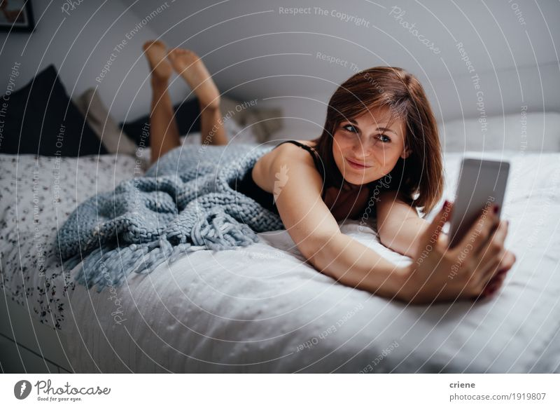 Young female adult laying on bed at home taking selfie Human being Woman Youth (Young adults) Young woman Relaxation Joy 18 - 30 years Adults Lifestyle Feminine Happy Modern Technology Smiling Cellphone Home
