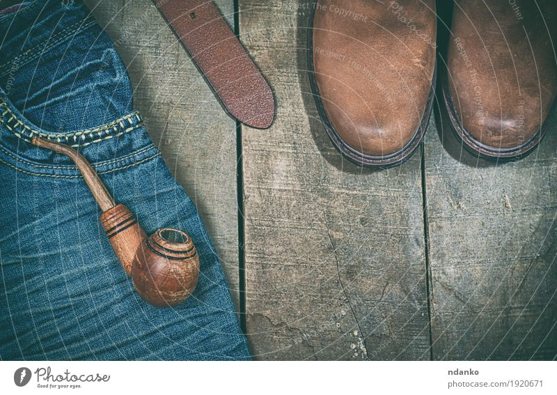 Blue jeans, boots with wooden smoking pipe Clothing Workwear Jeans Leather Belt Footwear Boots Wood Old Modern Retro Brown Fashion empty space vintage Shabby