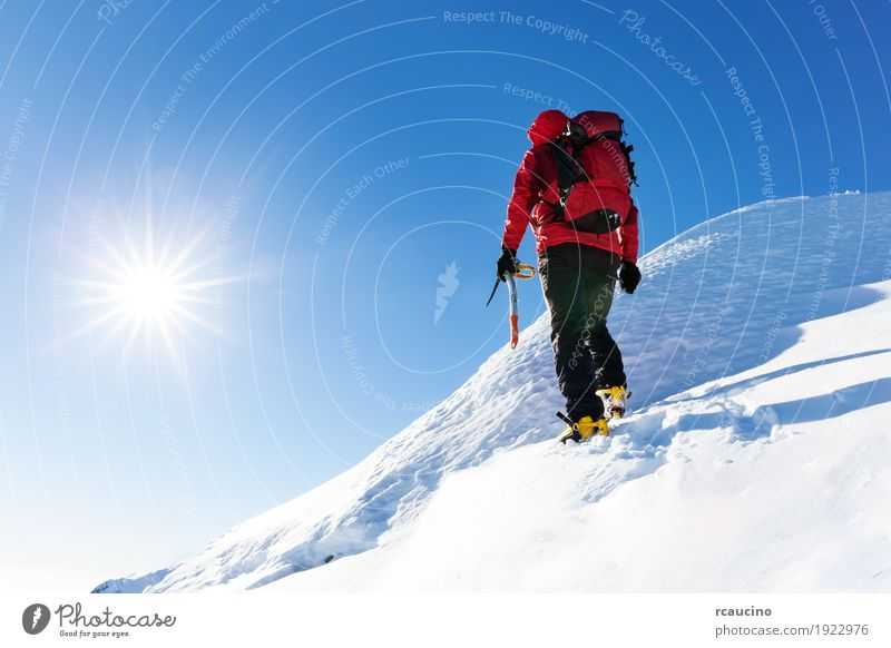 Climber reaches the top of a snowy peak Human being Nature Vacation & Travel Man Colour Landscape Red Loneliness Winter Mountain Adults Snow Sports Copy Space