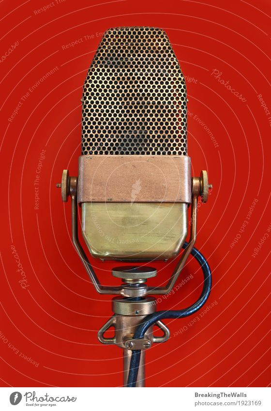 Vintage old retro vocal metal microphone over red Red Metal Retro Music Technology Historic Cable Concert Microphone Hardware Antique Voice Bronze Interview