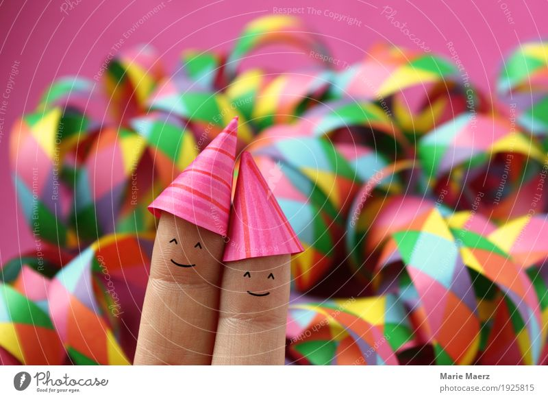 Couples with party hats in front of colorful streamers Joy Party Feasts & Celebrations New Year's Eve Human being Woman Adults Man Fingers 2 Hat Laughter Funny