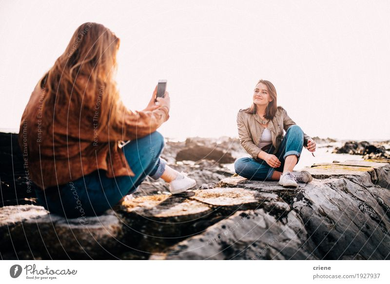 Teenager girl taking photo with smartphone of her friend Human being Woman Youth (Young adults) Young woman Ocean Clouds Joy Beach Adults Lifestyle Feminine Rock Together Friendship Sit Technology
