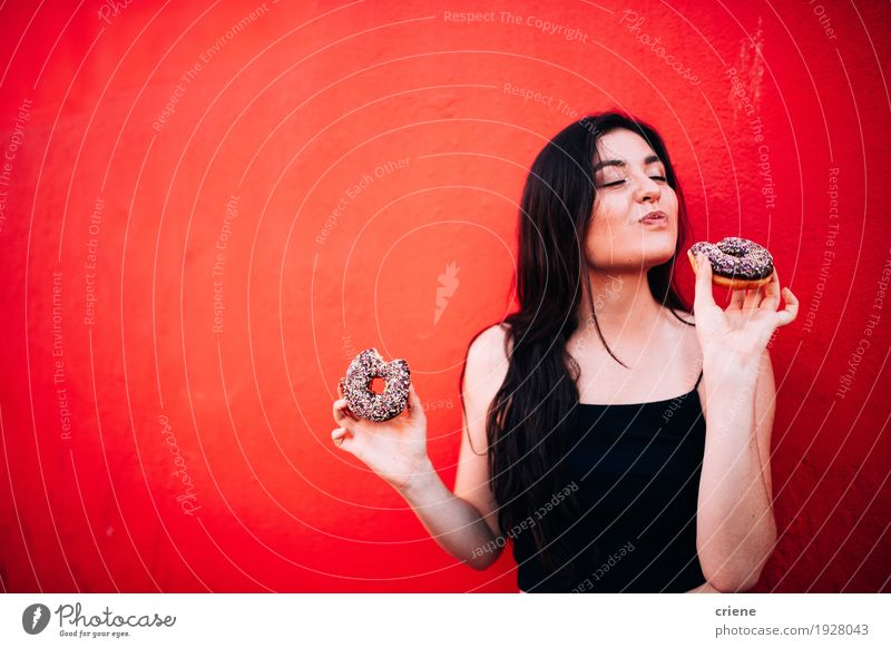 Young happy caucasian girl eating chocolate donuts Human being Woman Youth (Young adults) Young woman Red Joy Adults Eating Lifestyle Feminine Food Copy Space Stand Happiness To enjoy Smiling