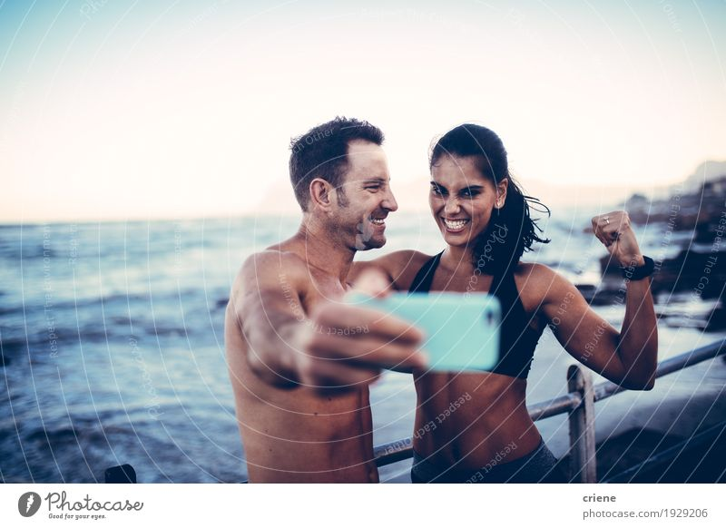 young athlete couple taking selfie with smartphone Youth (Young adults) Young woman Young man Ocean Joy Beach Lifestyle Sports Couple Together Waves Happiness Fitness Telephone Posture Camera