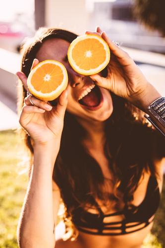 Young women holding oranges in front of her face Food Fruit Orange Lifestyle Joy Relaxation Summer Summer vacation Sun Sunbathing Garden Feminine Young woman