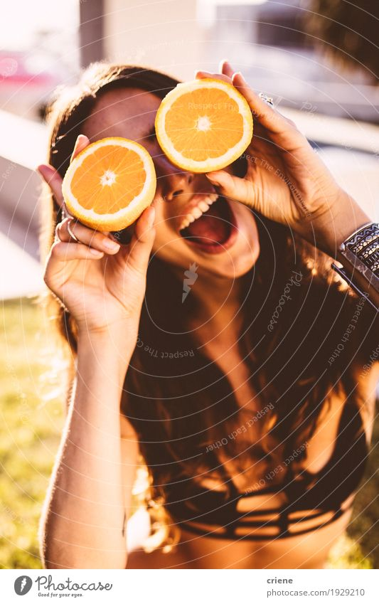 Young women holding oranges in front of her face Youth (Young adults) Summer Young woman Sun Relaxation Joy Emotions Lifestyle Feminine Garden Food Fruit Fresh Orange Happiness To enjoy