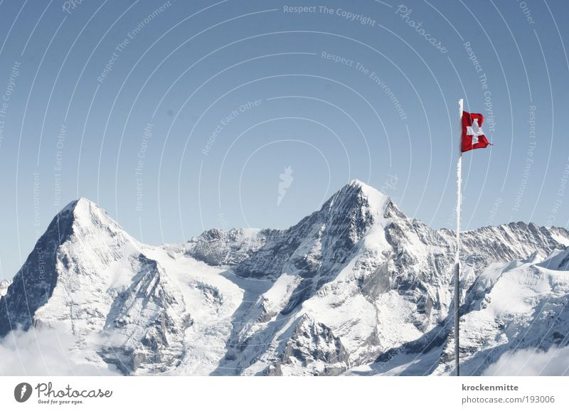 The heart of Switzerland Environment Nature Landscape Winter Beautiful weather Snow Hill Rock Alps Mountain Peak Snowcapped peak Flag Flagpole Crucifix