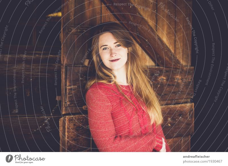 Young woman leans against wooden door and is happy Feminine Youth (Young adults) Life 1 Human being 18 - 30 years Adults Sweater Brunette Blonde Long-haired